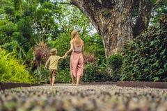 Madre e hijo que caminan en un pavimento de adoquín texturizado, Reflexolog Fotos de archivo libres de regalías