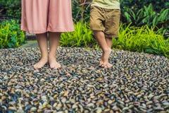 Madre e hijo que caminan en un pavimento de adoquín texturizado, Reflexolog Foto de archivo