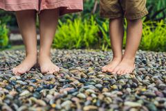 Madre e hijo que caminan en un pavimento de adoquín texturizado, Reflexolog Imagen de archivo libre de regalías