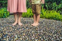 Madre e hijo que caminan en un pavimento de adoquín texturizado, Reflexology Piedras del guijarro en el pavimento para el reflexo Fotografía de archivo