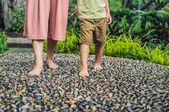 Madre e hijo que caminan en un pavimento de adoquín texturizado, Reflexology Piedras del guijarro en el pavimento para el reflexo Imagen de archivo libre de regalías