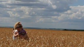 Madre e hijo que corren en el campo de trigo Una familia feliz metrajes