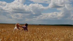 Madre e hijo que corren en el campo de trigo Una familia feliz almacen de video