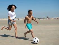 Madre e hijo que corren en la playa con la bola Fotos de archivo