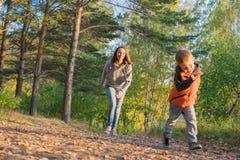 Madre e hijo que corren en la trayectoria en bosque del otoño Imágenes de archivo libres de regalías