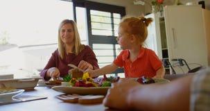 Madre e hijo que cortan una barra de pan en la mesa de comedor 4k almacen de metraje de vídeo
