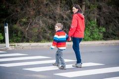 Madre e hijo que cruzan la calle Imágenes de archivo libres de regalías