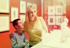 Madre e hijo que disfrutan de exposiciones en museo Fotografía de archivo