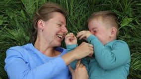 Madre e hijo que engañan alrededor la mentira en la hierba Riendo, divirti?ndose almacen de metraje de vídeo