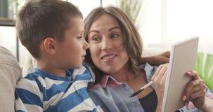 Madre e hijo que escriben la lista de compras en libreta metrajes