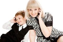 Madre e hijo que hablan sobre los teléfonos celulares Imágenes de archivo libres de regalías
