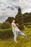 Madre e hijo que hacen girar en parque del verano Caliéntese entonado Imagenes de archivo