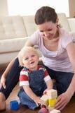 Madre e hijo que juegan con los bloques coloreados en Hom imagen de archivo libre de regalías
