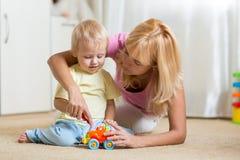 Madre e hijo que juegan con los coches del juguete dentro Foto de archivo libre de regalías