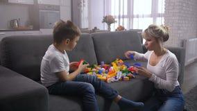 Madre e hijo que juegan el constructor del juguete en casa almacen de metraje de vídeo