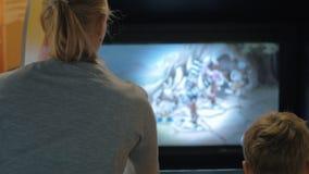 Madre e hijo que juegan en la máquina de la diversión almacen de metraje de vídeo