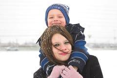 Madre e hijo que juegan en la nieve imagen de archivo libre de regalías