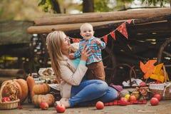 Madre e hijo que juegan en la yarda en el pueblo Fotografía de archivo libre de regalías