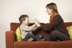 Madre e hijo que juegan en un sofá Fotos de archivo