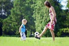 Madre e hijo que juegan la bola en el parque. Foto de archivo libre de regalías