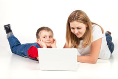 Madre e hijo que mienten en el suelo con la computadora portátil Imágenes de archivo libres de regalías