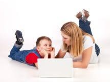 Madre e hijo que mienten en el suelo con la computadora portátil Foto de archivo libre de regalías
