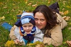 Madre e hijo que mienten en hierba Foto de archivo