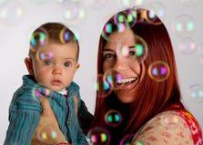 Madre e hijo que miran burbujas Fotografía de archivo