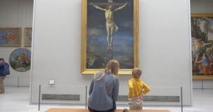 Madre e hijo que miran la pintura con la crucifixión almacen de metraje de vídeo