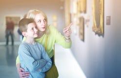 Madre e hijo que miran pinturas en pasillos del museo Foto de archivo