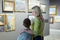 Madre e hijo que miran pinturas en pasillos del museo Fotos de archivo