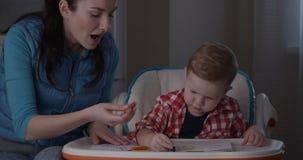 Madre e hijo que pasan el tiempo junto que dibuja con los creyones coloreados de los lápices almacen de video