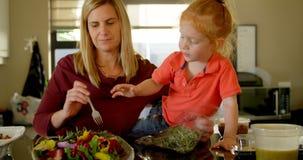 Madre e hijo que preparan la ensalada en la cocina 4k almacen de metraje de vídeo
