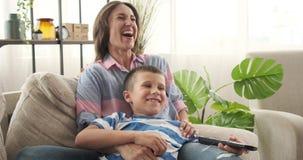 Madre e hijo que ríen mientras que mira película en casa almacen de metraje de vídeo