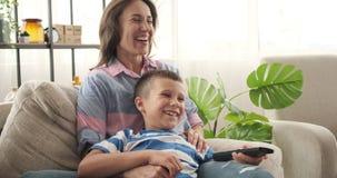 Madre e hijo que ríen mientras que ve la TV en casa almacen de metraje de vídeo