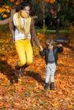 Madre e hijo que saltan en parque Imágenes de archivo libres de regalías