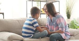 Madre e hijo que se divierten en el sofá en casa metrajes