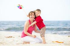 Madre e hijo que se divierten en la playa. Foto de archivo