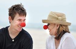 Madre e hijo que se divierten que ríe celebrando día rojo de la nariz en día de fiesta hermoso de la playa