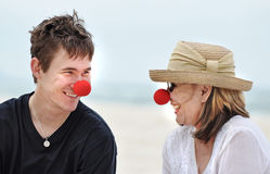 Madre e hijo que se divierten que ríe celebrando día rojo de la nariz en día de fiesta hermoso de la playa Fotos de archivo