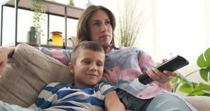 Madre e hijo que se divierten que ve la TV en casa almacen de video