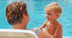 Madre e hijo que se relajan en sunbed cerca de piscina en el centro turístico metrajes