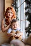 Madre e hijo que se sientan cerca de la ventana en el cuarto con las decoraciones de la Navidad Fotos de archivo libres de regalías