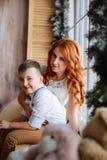 Madre e hijo que se sientan cerca de la ventana en el cuarto con las decoraciones de la Navidad Imagen de archivo