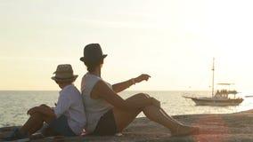 Madre e hijo que se sientan de nuevo a la parte posterior en el banco de mar rocoso y notada el yate flotante al lado de la costa almacen de metraje de vídeo
