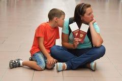 Madre e hijo que se sientan en el piso con los boletos para el vuelo Fotos de archivo libres de regalías