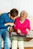 Madre e hijo que se sientan en el sofá y que miran algo en el ordenador portátil Foto de archivo