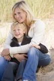 Madre e hijo que se sientan en la sonrisa de la playa fotos de archivo libres de regalías
