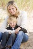 Madre e hijo que se sientan en la sonrisa de la playa fotografía de archivo libre de regalías