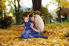 Madre e hijo que se sientan en las hojas caidas en parque Foto de archivo